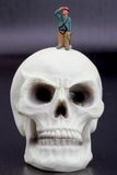 Hikers miniature figurine and human skull Royalty Free Stock Images