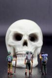 Hikers miniature figurines and human skull Royalty Free Stock Photography