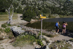 Hikers on a mountain lake shore Stock Photos