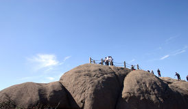 Hikers on mountain summit. Hikers and tourists walking on summit of rocky mountain with blue sky background Stock Photography