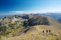 Hikers in mountains. Three hikers on the trek in Rila mountains, Bulgaria Stock Photos