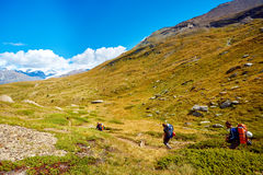 Hikers in the mountains. Hikers with backpacks on the trail in the Apls mountains. Trek near Matterhorn mount Royalty Free Stock Image