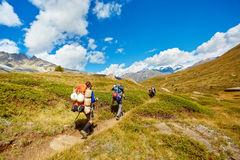 Hikers in the mountains. Hikers with backpacks on the trail in the Apls mountains. Trek near Matterhorn mount Royalty Free Stock Images