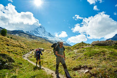 Hikers in the mountains. Hikers with backpacks on the trail in the Apls mountains. Trek near Matterhorn mount Stock Photo