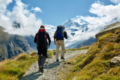 Hikers in the mountains. Hikers with backpacks on the trail in the Apls mountains. Trek near Matterhorn mount Stock Image