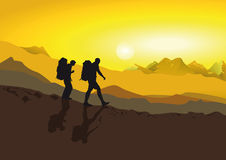 Hikers in the mountains. Hikers with haversacks seen in silhouette coming down a mountain at sunset in golden light Stock Image