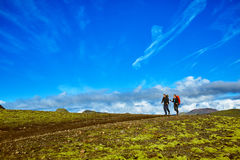 Hikers in the mountains, Iceland. Hikers on the trail in the Islandic mountains. Trek in National Park Landmannalaugar, Iceland. valley is covered with bright Stock Image