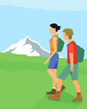 Hikers in mountains. Man and woman hiking across green fields in foot of mountains with backpacks Stock Image