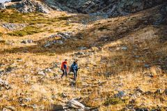 Hikers in the mountains. Tourists descend from the mountain. Couple of hikers in the mountains. Tourists women and men descend from mountain Royalty Free Stock Images