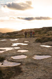 Hikers Near Rock Pools. Rock pools under a dramatic sky, with a small group of hikers walking in the distance.  Taken on a hiking trail in Central South Africa Royalty Free Stock Images