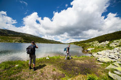 Hikers nearby a lake in the mountains Stock Images