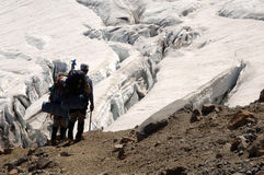 Hikers overlooking crevasse Stock Photos