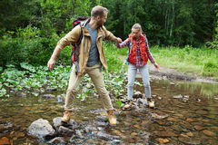 Hikers passing river. Affectionate couple passing river in the forest Royalty Free Stock Photography