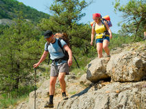 Hikers on a path. Hikers go down on a stony track stock image