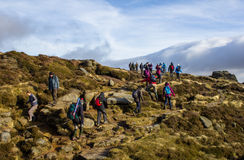 Hikers in the Peak District. LONDON, UK - 16TH NOVEMBER 2014: Hikers in the Peak District walking up a rocky hill Royalty Free Stock Images