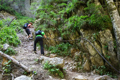 Hikers on a perilous trail, holding the safety line Royalty Free Stock Images