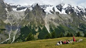Hikers picnicking beneath snow-capped French Alps. Hikers picnic on green field beneath snow-capped dark peaks of the French Alps, in Mont Blanc range Royalty Free Stock Photo