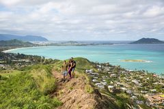 Hikers posing for a portrait with the view of Lanikai from a top. A group of friends posing for a portrait with the view of Lanikai from a top the Pillbox hiking Stock Photos