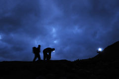 Hikers prepare to ascend Scafell Pike at night. Three Hikers prepare to ascend Scafell Pike at night Stock Photo