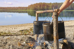 Preparing food on fire in a hike. Hikers preparing breakfast on fire on the riverside in sunny morning Stock Photography