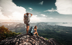 Hikers relax on top of a mountain. And enjoy valley greate view Royalty Free Stock Photos