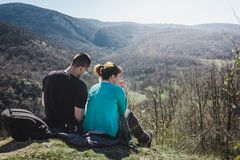 Hikers relaxing on top of a mountain and enjoying sun. stock images