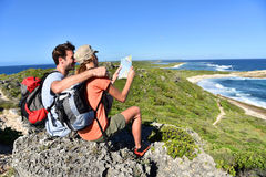 Hikers relaxing after a walk admiring sea view Royalty Free Stock Images