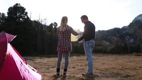 Hikers returning to camp, check map stock footage