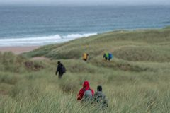 Hikers at Sandwood Bay, Highlands of Scotland. Remote bay with white sand, dunes and reeds. royalty free stock photos