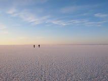 Hikers on a sea ice. Vast field Stock Photo