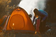 Hikers set the tent. And make fire in the wild area royalty free stock images