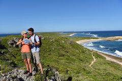Hikers sightseeing the islands. Couple of hikers looking at map and scenery stock photography