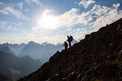 Hikers silhouette on a mountain slope