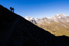 Hikers silhouettes in the mountains Stock Photo