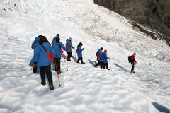 Hikers in single file descending icy slope at glacier exploration royalty free stock images