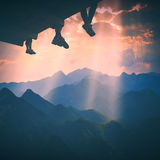 Hikers sit above the valley. Instagram stylisation. Hikers sit on a wooden flooring above the mountain valley and enjoy golden sunset. Instagram stylisation Royalty Free Stock Photos