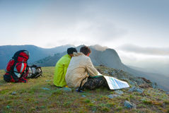 Hikers sit on the peak Royalty Free Stock Images