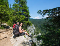 Hikers sitting on the edge of a very high cliff Royalty Free Stock Image