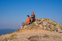 Hikers are sitting on the top of the mountain and look at the vi Royalty Free Stock Images