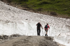 Hikers between snow in Koednitz Valley, Austria Royalty Free Stock Images