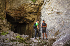 Hikers standing at the entrance of a cave Stock Image