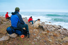 Hikers on a stony sea shore Royalty Free Stock Photo