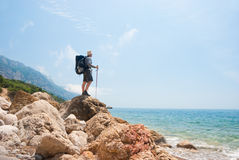 Hikers on a stony sea shore. Enjoys a landscape Royalty Free Stock Images