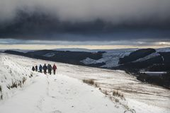 Several hikers in stormy winter landscape in Brecon Beacons Stock Photos