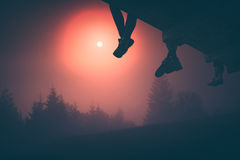 Hikers and sunrise. Instagram stylisation. Hikers sit on a wooden flooring above the valley covered with fog. Early morning time. Instagram stylisation Royalty Free Stock Photography