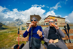Hikers at the top of a pass. With backpack enjoy sunny day in Alps. Hikers having rest and eating.  Switzerland, Trek near Matterhorn mount Stock Photo