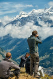 Hikers at the top of a pass. With camera enjoy sunny day in Alps. Switzerland, Trek near Matterhorn mount Stock Photos