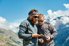 Hikers at the top of a pass. With smartphone and action camera enjoy sunny day in Alps. Switzerland, Trek near Matterhorn mount. try to configure the device to Stock Photos