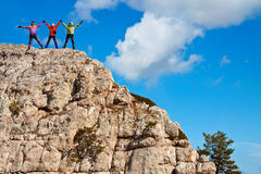Hikers at the top of a rock with their hands up Royalty Free Stock Images