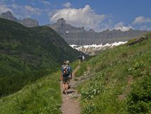 Hikers on the Trail. This picture of the hikers was taken on the Ptarmingan Tunnel / Iceberg Lake trail in Glacier National Park Stock Image
